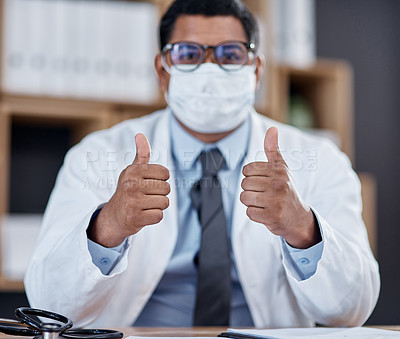 Buy stock photo Portrait of a young doctor wearing a face mask and showing thumbs up in his office