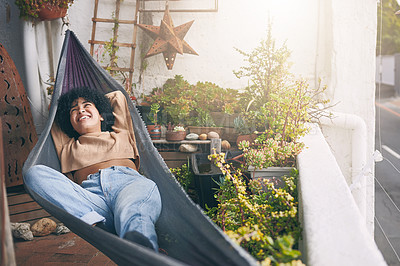 Buy stock photo Shot of a young woman relaxing on a hammock outdoors
