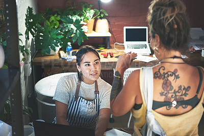 Buy stock photo Shot of two young women using a laptop while working together in a pottery studio