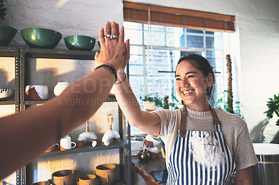 Buy stock photo Shot of two young women giving each other a high five in a pottery studio