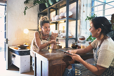 Buy stock photo Shot of two young women using a digital tablet during a meeting in a pottery studio