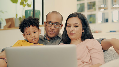Buy stock photo Shot of a family of three using a laptop while sitting together at home