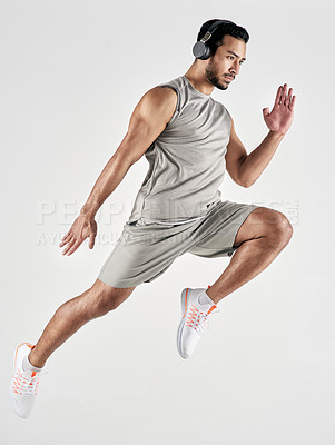 Buy stock photo Studio shot of a sporty young man wearing headphones and jumping against a white background