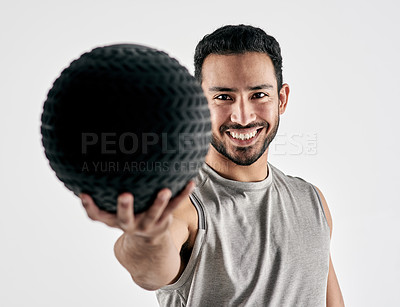 Buy stock photo Studio portrait of a muscular young man holding an exercise ball against a white background