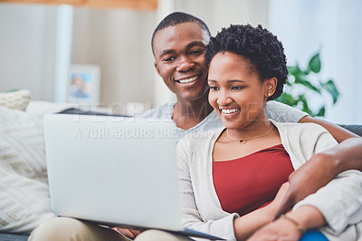 Buy stock photo Cropped shot of a smiling young loving couple browsing on a laptop together while sitting on the couch in their apartment