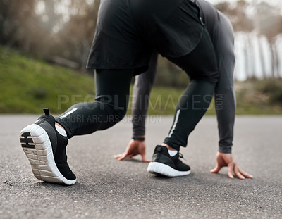 Buy stock photo Cropped shot of an unrecognizable man crouched down in a starters position before exercising outside