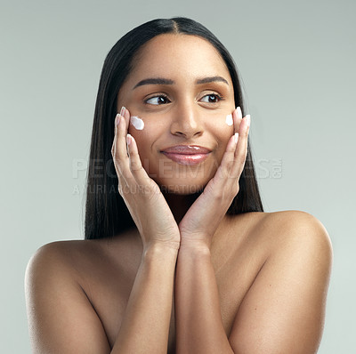 Buy stock photo Shot of a beautiful young woman applying moisturiser to her skin