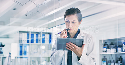 Buy stock photo Shot of a young woman using a digital tablet while writing notes on a glass screen in a lab