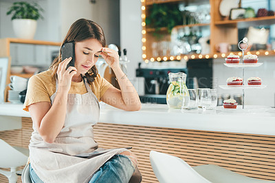 Buy stock photo Shot of a young woman using a smartphone and feeling stressed while working in a cafe