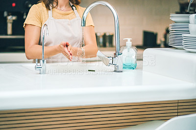 Buy stock photo Shot of an unrecognisable woman washing her hands while working in a cafe