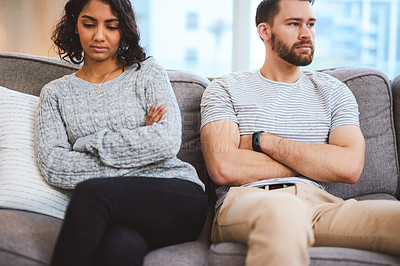 Buy stock photo Cropped shot of a young couple giving each other the silent treatment during a fight at home