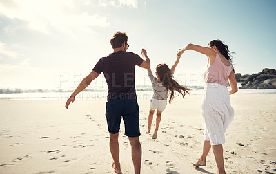 Buy stock photo Shot of a couple being playful while at the beach with their daughter