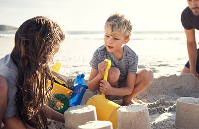 Buy stock photo Shot of a little boy and girl building sandcastles on the beach