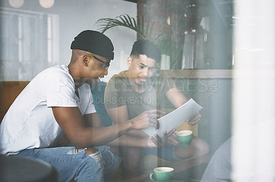 Buy stock photo Shot of two young men discussing business while sitting together in a coffee shop
