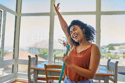 Buy stock photo Shot of a young woman singing while cleaning her home