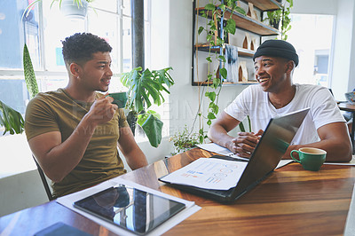 Buy stock photo Cropped shot of two handsome friends sitting together in a coffeeshop and having a discussion