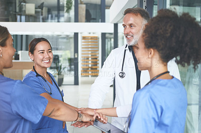 Buy stock photo Cropped shot of a diverse group of healthcare professionals standing huddled together with their hands piled in the middle