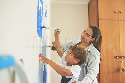 Buy stock photo Shot of a woman and her son painting a room blue at home