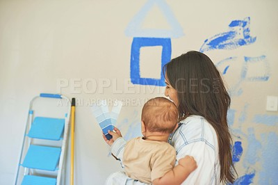 Buy stock photo Shot of a woman looking at paint swatches while holding her baby at home