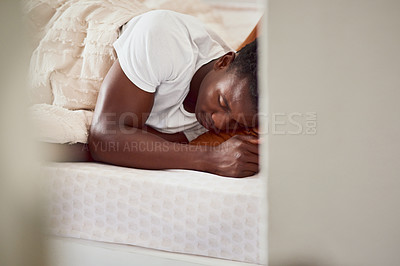 Buy stock photo Shot of a young man sleeping in his bed at home