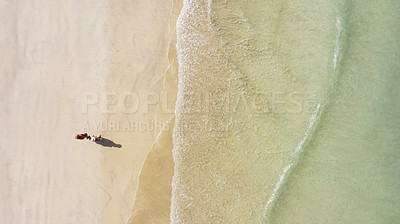 Buy stock photo High angle shot of an affectionate couple walking on the beach on a summer's day