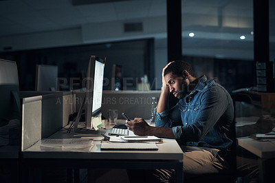 Buy stock photo Shot of a young businessman looking stressed while using a smartphone during a late night in a modern office