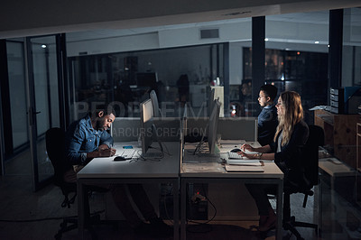 Buy stock photo Shot of a group of young businesspeople using their computers during a late night in a modern office