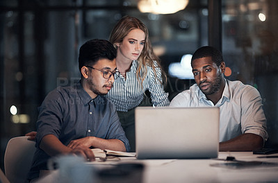 Buy stock photo Shot of a team of young businesspeople using a laptop during a late night meeting in a modern office