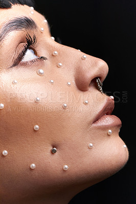 Buy stock photo Studio shot of a beautiful young woman with pearls on her face posing against a black background