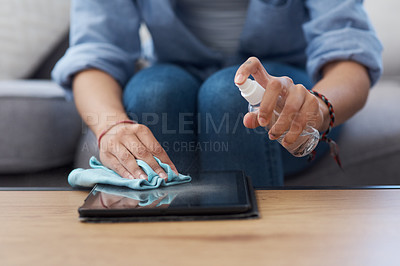 Buy stock photo Shot of an anonymous woman spraying down a tablet to disinfect it