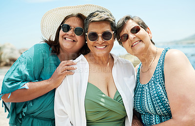 Buy stock photo Shot of a mature group of friends standing together during a day out on the beach