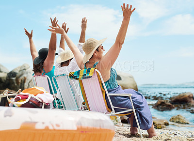 Buy stock photo Shot of a mature group of friends sitting together and raising her arms during a day on the beach