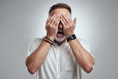 Buy stock photo Studio shot of a mature man covering his eyes and looking shocked against a grey background
