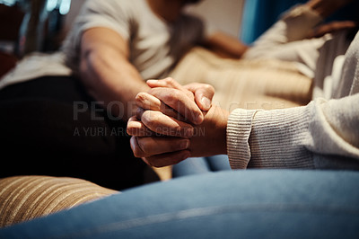Buy stock photo Cropped shot of a young couple holding hands while sitting together at home