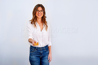 Buy stock photo Shot of an attractive young businesswoman standing alone against a white wall and holding out her credit card
