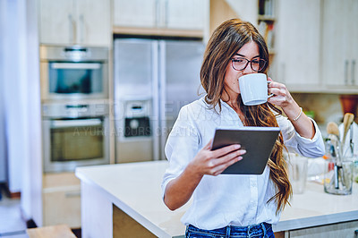Buy stock photo Shot of a young woman having coffee and using a digital tablet at home