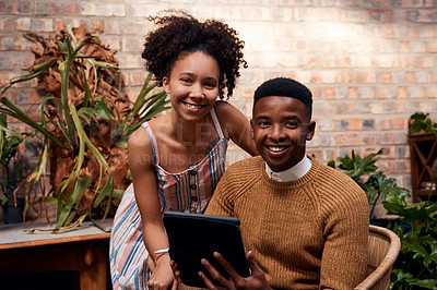 Buy stock photo Portrait of a young man and woman using a digital tablet while working in a garden centre