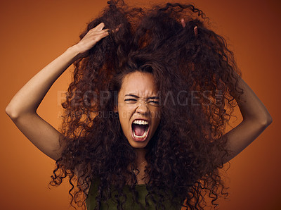 Buy stock photo Shot of a woman with curly hair feeling frustrated while standing against an orange background