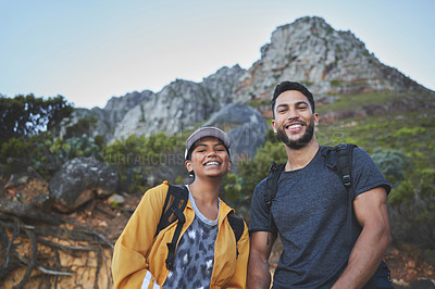Buy stock photo Shot of a young couple hiking on a mountain range outdoors