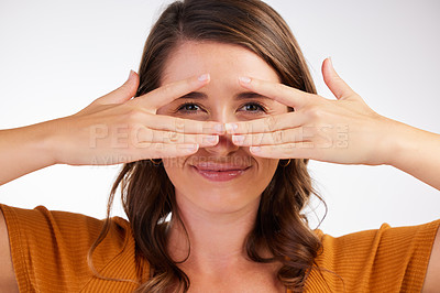 Buy stock photo Studio shot of a young woman covering her face with her hands against a white background