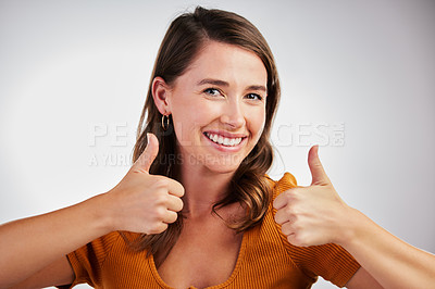 Buy stock photo Studio shot of a young woman showing thumbs up against a white background