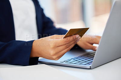 Buy stock photo Shot of a woman sitting at her desk doing online shopping