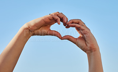 Buy stock photo Cropped shot of a woman forming a heart shape with her hands against a blue sky