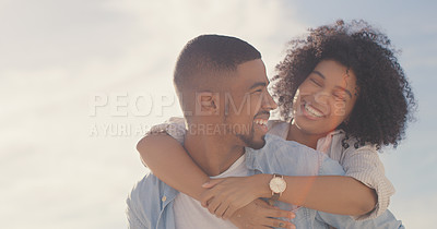 Buy stock photo Shot of a man carrying his girlfriend on his back while spending the day outdoors