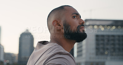 Buy stock photo Cropped shot of a handsome young man looking thoughtful while standing outside in the city