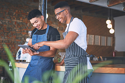 Buy stock photo Shot of two young men using a digital tablet while working in a cafe