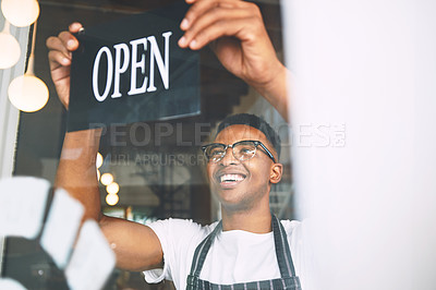 Buy stock photo Shot of a young man hanging up an open sign while working in a cafe