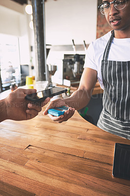 Buy stock photo Shot of a man using a smartphone to make a payment in a cafe