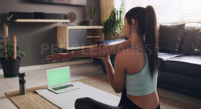 Buy stock photo Shot of an anonymous woman using her laptop to do a stretch routine before working out at home