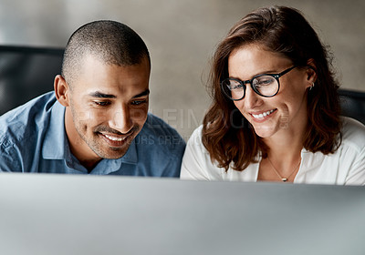 Buy stock photo Shot of two young businesspeople sitting together in the office and using a computer